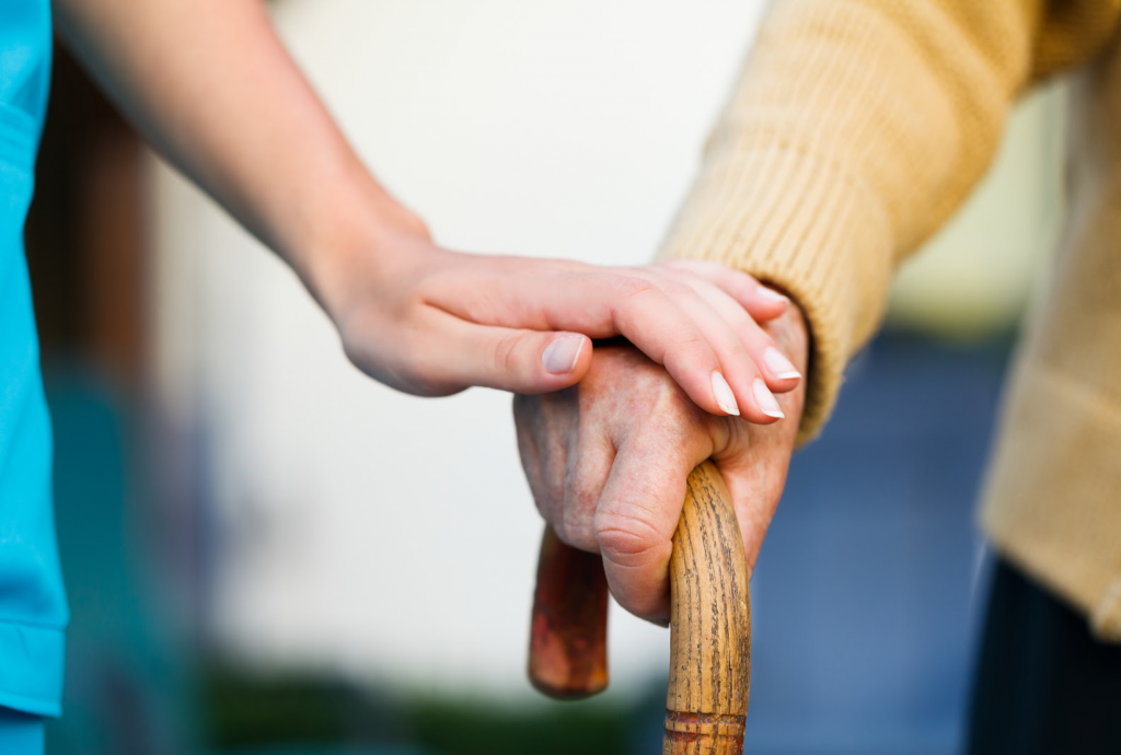 A woman holding another's hand in a caring manner.